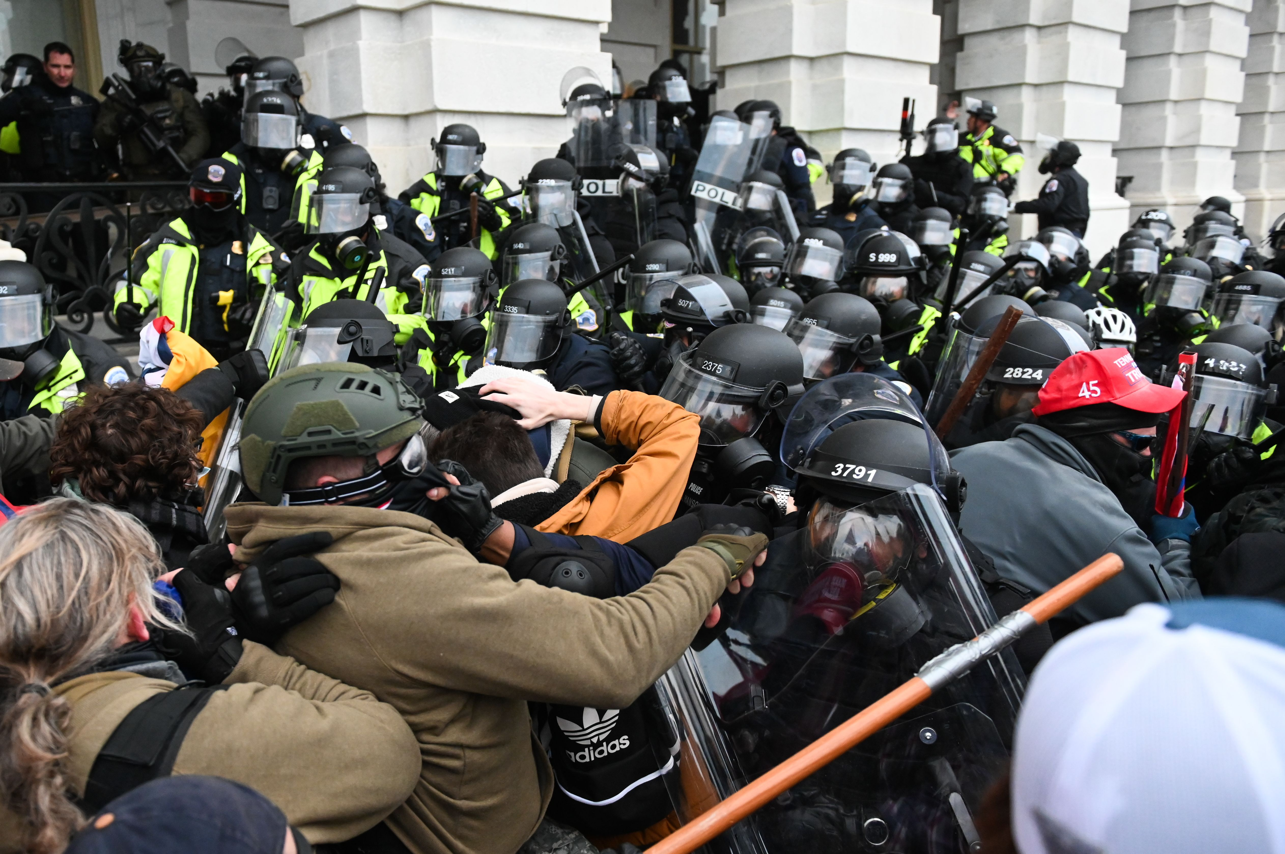 Riot police push back a crowd on January 6, 2021 at the Capitol building in Washington, DC. (Photo by ROBERTO SCHMIDT/AFP via Getty Images)