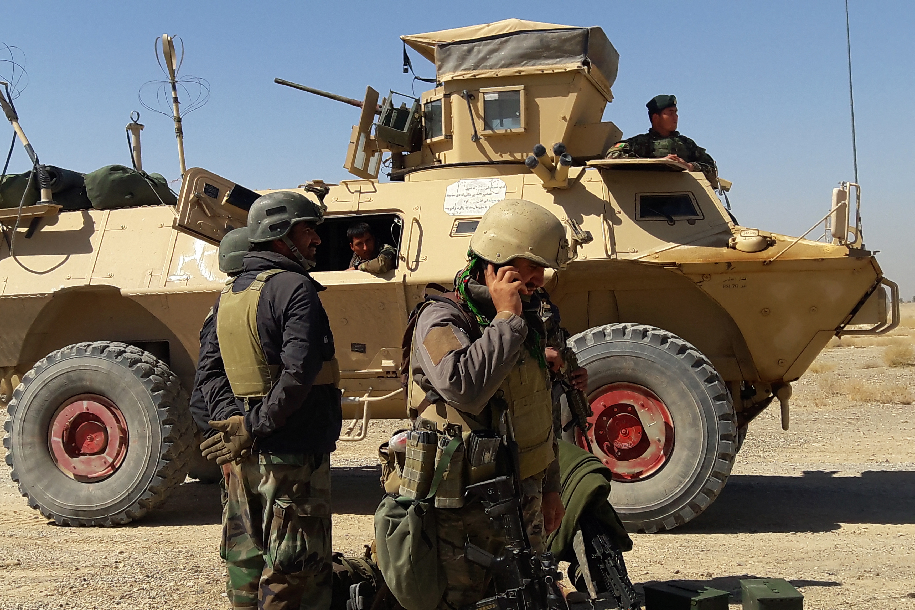 Afghan security forces stand near an armoured vehicle during ongoing fighting between Afghan security forces and Taliban fighters in the Busharan area on the outskirts of Lashkar Gah, the capital city of Helmand province. (Photo by SIFATULLAH ZAHIDI/AFP via Getty Images)