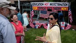 """People talk before the start of a rally against """"critical race theory"""" (CRT) being taught in schools at the Loudoun County Government center in Leesburg, Virginia"""