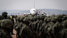 """Rwandan soldiers from Rwanda Defence Forces (RDF) and Rwandan policemen prepare to board a """"Rwandair"""" plane for a military mission to Mozambique at Kanombe airport, Kigali, Rwanda on July 10, 2021. - The mission, which includes a contingent of 1,000 soldiers and police, is aimed at helping the country fight extremist militants who are wreaking havoc in the gas-rich north of the nation, at the request of the Mozambican government. (Photo by Simon Wohlfahrt / AFP) (Photo by SIMON WOHLFAHRT/AFP via Getty Images)"""