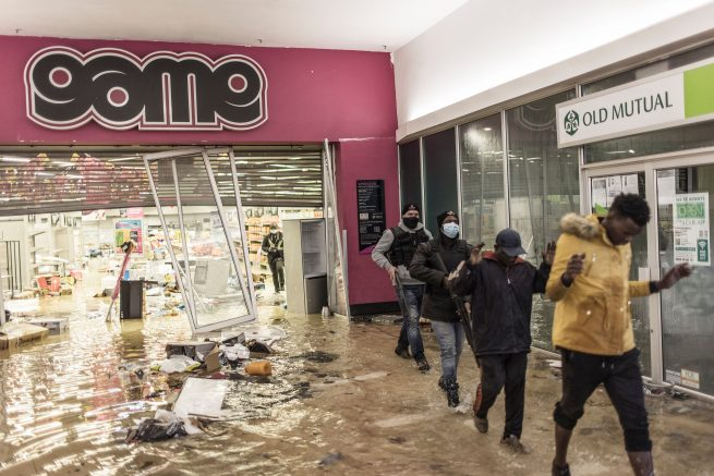 Suspected looters who surrendered to armed private security officers are marched outside, in a flooded mall in Vosloorus. (Photo by MARCO LONGARI/AFP via Getty Images)