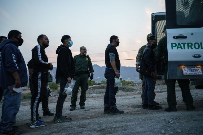 Migrants caught crossing the US-Mexico border are loaded into a transport van by US Border Patrol agents in Sunland Park, New Mexico. (Photo by PAUL RATJE/AFP via Getty Images)