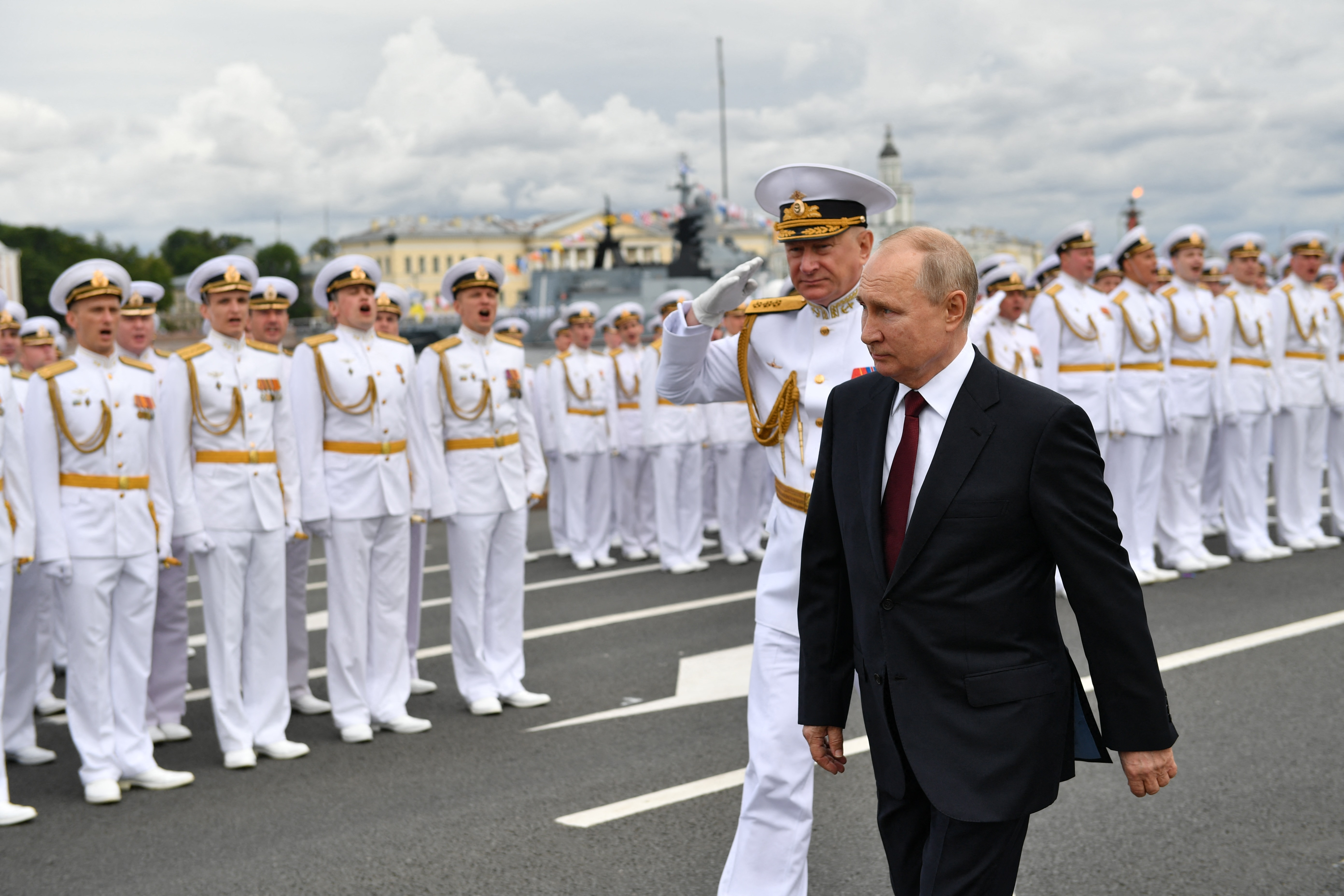 Russian President Vladimir Putin, right, and Commander-in-Chief of the Russian Navy, Admiral Nikolai Yevmenov, second right, arrive to attend the Navy Day parade in St. Petersburg on July 25, 2021. (Photo by ALEXEY NIKOLSKY/SPUTNIK/AFP via Getty Images)