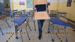 """A worker sets up desks and chairs on September 4, 2020 in a classroom of the Luigi Einaudi technical high school in Rome prior to its reopening, during the the COVID-19 infection, caused by the novel coronavirus. - Millions of Italian pupils go back to the benches next week after six months at home, confronting a new reality of outdoor classes, coronavirus """"isolation rooms"""" and even a possible ban on singing. (Photo by Vincenzo PINTO / AFP) (Photo by VINCENZO PINTO/AFP via Getty Images)"""