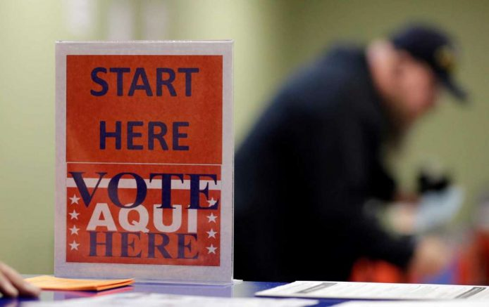 In this Feb. 26, 2014 photo, a voter prepares to cast his ballot at an early voting polling site, in Austin, Texas. (AP Photo/Eric Gay)