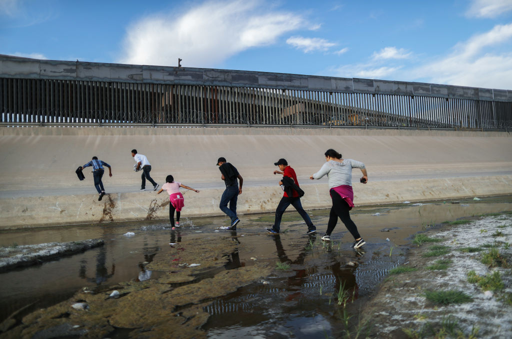 CIUDAD JUAREZ, MEXICO - MAY 19: Migrants cross the border between the U.S. and Mexico at the Rio Grande river, as they enter El Paso, Texas, on May 19, 2019 as taken from Ciudad Juarez, Mexico. The location is in an area where migrants frequently turn themselves in and ask for asylum in the U.S. after crossing the border. Approximately 1,000 migrants per day are being released by authorities in the El Paso sector of the U.S.-Mexico border amidst a surge in asylum seekers arriving at the Southern border. (Photo by Mario Tama/Getty Images)
