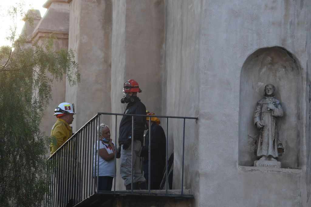 A Los Angeles Fire Department arson investigator (R) and others work at the San Gabriel Mission after a fire early on July 11, 2020, in San Gabriel, California. - The roof of the mission was completely destroyed while the interior of the structure sustained significant damage, US media reported. An investigation into the cause of the fire is underway, according to the San Gabriel Police Department. (Photo by Robyn Beck / AFP) (Photo by ROBYN BECK/AFP via Getty Images)