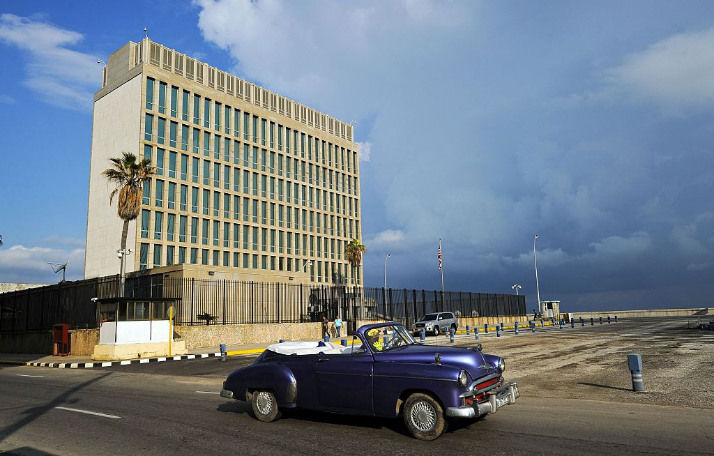 File picture showing a vintage US car passing in front of the US Embassy in Havana on December 17, 2015. Granma, the Communist Party newspaper and a source of anti-US tirades since 1965, made history on September 21, 2016 by running a US embassy notice for American citizens living in Cuba.The notice gives information on how US residents can request absentee ballots to vote in the November 8 presidential election. / AFP / YAMIL LAGE / FILES (Photo credit should read YAMIL LAGE/AFP via Getty Images)