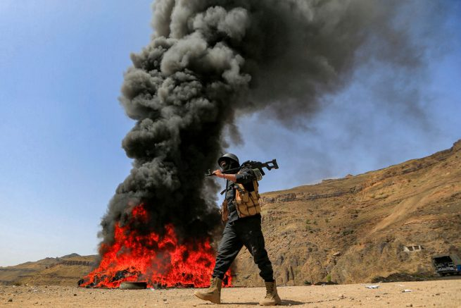 """A member of security forces loyal to Yemen's Huthi rebels walks past a bonfire incinerating seized narcotic substances, in the Huthi-held capital on June 26, 2021, the United Nations' designated """"International Day Against Drug Abuse and Illicit Trafficking"""". (Photo by Mohammed HUWAIS / AFP) (Photo by MOHAMMED HUWAIS/AFP via Getty Images)"""