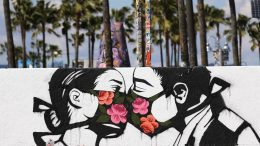 VENICE, CALIFORNIA - MARCH 21: Palm trees stand behind a street art piece by artist Pony Wave depicting two people kissing while wearing face masks on Venice Beach on March 21, 2020 in Venice, California. California Governor Gavin Newsom issued a 'stay at home' order for California's 40 million residents in order to slow the spread of coronavirus (COVID-19). Californians may still go to the beach without violating Newsom's order as long as they maintain social distancing and adhere to other public health measures related to the coronavirus. (Photo by Mario Tama/Getty Images)