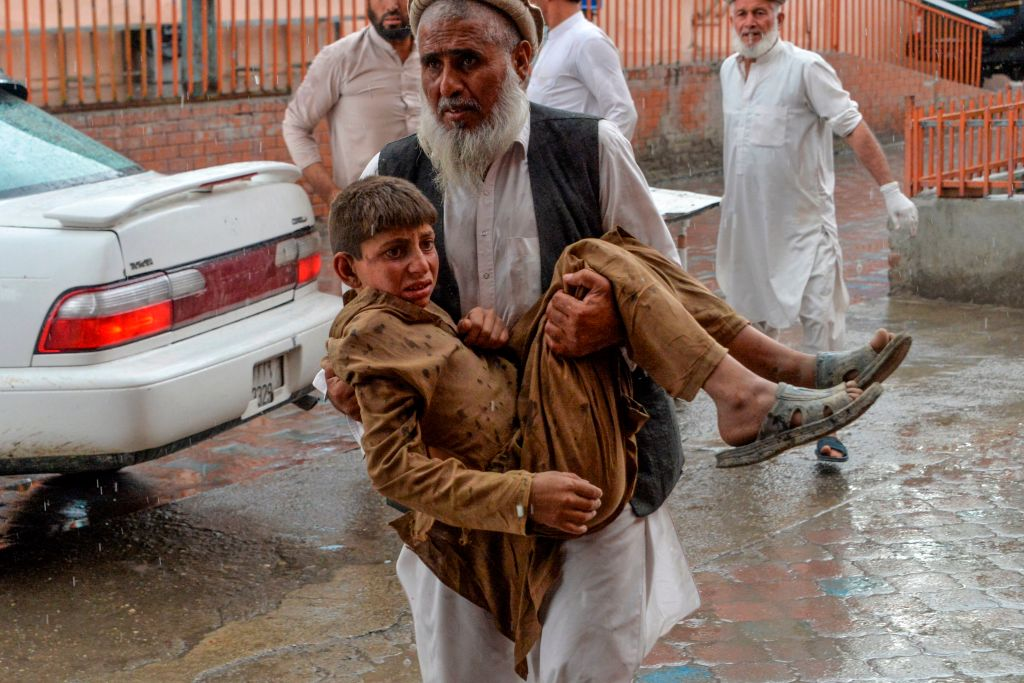 """TOPSHOT - A volunteer carries an injured youth to hospital, following a bomb blast in Haska Mina district of Nangarhar Province on October 18, 2019. - At least 28 worshippers were killed and dozens wounded by a blast inside an Afghan mosque during Friday prayers on October 18, officials said, a day after the United Nations said violence in the country had reached """"unacceptable"""" levels. (Photo by NOORULLAH SHIRZADA / AFP) (Photo by NOORULLAH SHIRZADA/AFP via Getty Images)"""