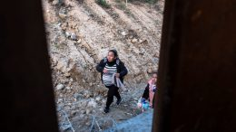 """TOPSHOT - A pregnant woman, part of a group of Central American migrants, walks after crossing the border fence from Tijuana in Mexico to San Diego County in the US, as seen from Tijuana, Baja California State, Mexico, on December 27, 2018. - America's border security head warned Wednesday officials were overwhelmed by the """"enormous flow"""" of families crossing from Mexico, appealing for federal health care funding after the second child in a month died in custody. (Photo by Guillermo Arias / AFP) (Photo credit should read GUILLERMO ARIAS/AFP via Getty Images)"""