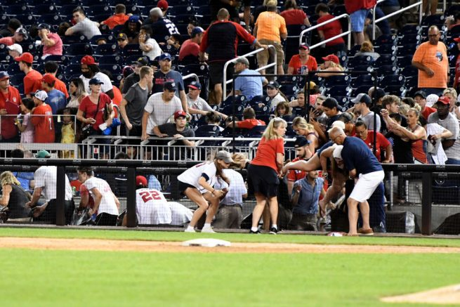 WASHINGTON, DC - JULY 17: Fans run for cover after what was believed to be shots were heard during a baseball game between the San Diego Padres the Washington Nationals at Nationals Park on July 17, 2021 in Washington, DC. (Photo by Mitchell Layton/Getty Images)