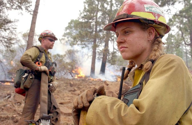 O'BRIEN, OR - AUGUST 4: Rogue River Hot Shots Megan Kruse (R) and Jason Barber (L) take a break after igniting a burnout in the Siskiyou National Forest August 4, 2002 in O'Brien, Oregon. Fire Crews continue to light burnout fires to try and stop a188,000 acre fire in the Siskiyou National Forest. (Photo by Justin Sullivan/Getty Images)