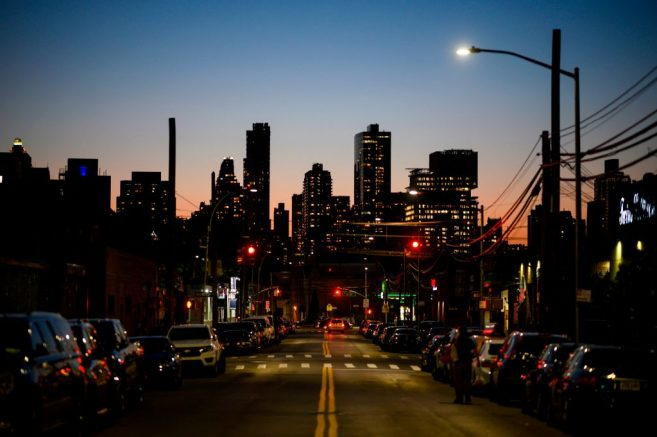 A man walks down a street in Queens with the skyline of Manhattan in the background on May 20, 2019 in New York City. (Photo by Johannes EISELE / AFP)        (Photo credit should read JOHANNES EISELE/AFP via Getty Images)