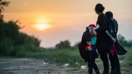 LA JOYA, TEXAS - JUNE 21: A migrant family watches the sunset while waiting to be accounted for and taken to a border patrol processing facility after crossing the Rio Grande into the U.S. on June 21, 2021 in La Joya, Texas. A surge of mostly Central American immigrants crossing into the United States has challenged U.S. immigration agencies along the U.S. Southern border. (Photo by Brandon Bell/Getty Images)