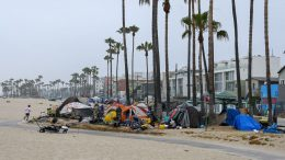 A man jogs along the beach as authorities prepare to begin clearing homeless encampments at the Venice Beach Boardwalk ahead of the Independence Day holiday weekend, July 2, 2021 in Los Angeles, California. - Authorities are offering unhoused people lining near the beach a path to permanent housing in an effort to clear the popular tourist destination of homeless camps before the July 4th holiday weekend. The number of homeless encampments along the popular tourist destination exploded during the coronavirus pandemic, making it a political flashpoint. (Photo by Robyn Beck / AFP) (Photo by ROBYN BECK/AFP via Getty Images)