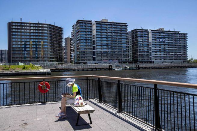 A woman sits on a bench across from the Tokyo 2020 Olympic village in Tokyo on July 18, 2021, ahead of the Olympic Games which begin on July 23. (Photo by Behrouz MEHRI / AFP) (Photo by BEHROUZ MEHRI/AFP via Getty Images)
