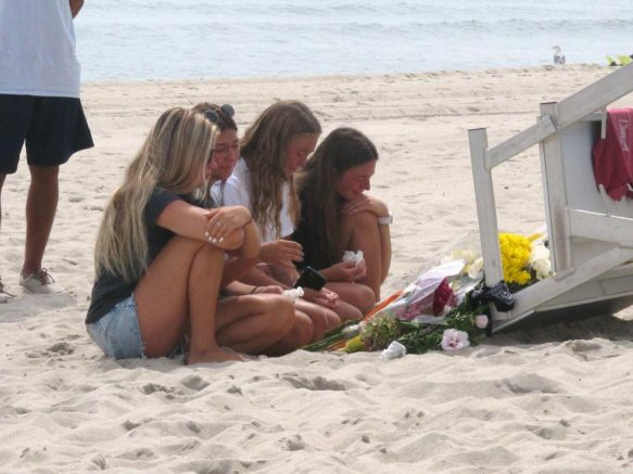 Friends and fellow lifeguards cry at the foot of a lifeguard stand in Berkeley Township, N.J., Tuesday Aug. 31, 2021, a day after 19-year-old lifeguard Keith Pinto was killed by lightning there. Pinto, of Toms River, was among eight people who were hit by lightning Monday afternoon in Berkeley Township. (AP Photo/Wayne Parry)