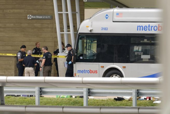 Police are looking at a scene and items are seen on the ground near a Metrobus outside the Pentagon Metro area, Tuesday, Aug. 3, 2021 at the Pentagon in Washington. (AP Photo/Andrew Harnik)