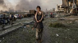 In this Aug. 4, 2020 file photo, Hoda Kinno, 11, is evacuated by her uncle Mustafa, in the aftermath of a massive explosion at the port in Beirut, Lebanon. (AP Photo/Hassan Ammar, File)