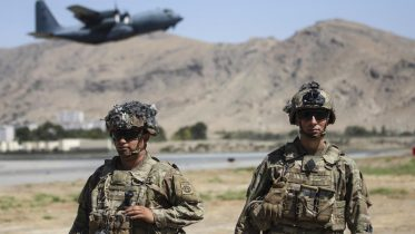 In this image provided by the Department of Defense, two paratroopers assigned to the 1st Brigade Combat Team, 82nd Airborne Division conduct security while a C-130 Hercules takes off during a evacuation operation in Kabul, Afghanistan. (Department of Defense via AP)