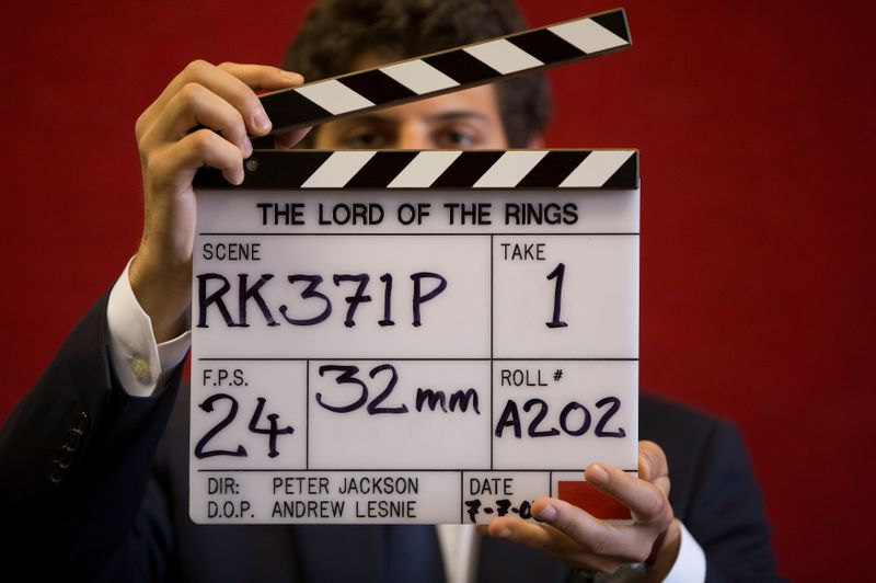 FILE PHOTO: A gallery assistant poses for a photograph with a clapper board used in the filming of the Lord of the Rings film 'Return of the King' in Bonhams auction house in London