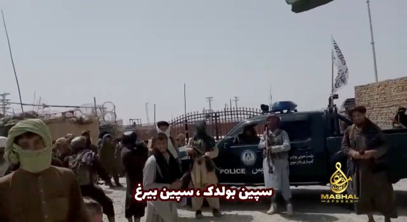 FILE PHOTO: People stand in front of a vehicle as an Islamic Emirate of Afghanistan and a Pakistan's flag flutter in front of the friendship gate of Afghanistan and Pakistan at the Wesh-Chaman border crossing