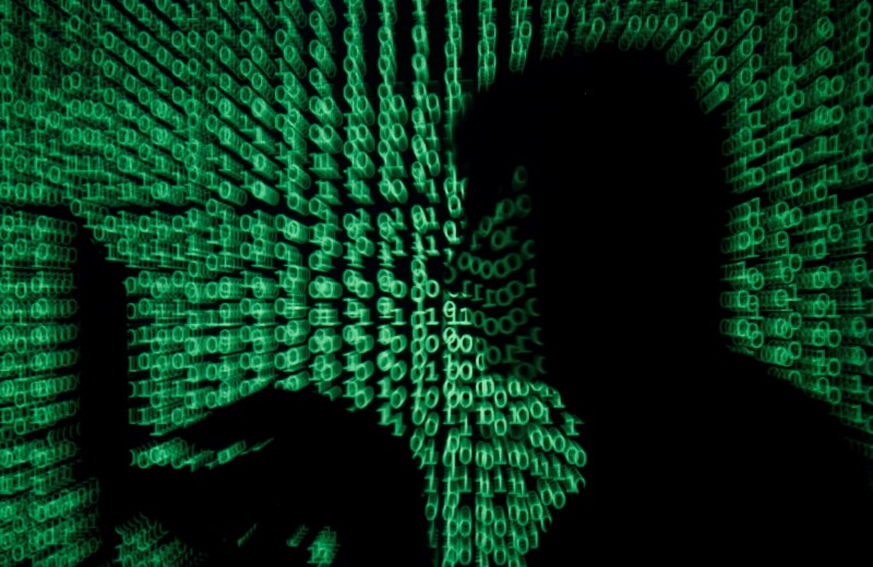 FILE PHOTO: A man holds laptop computer as cyber code is projected on him in this illustration picture