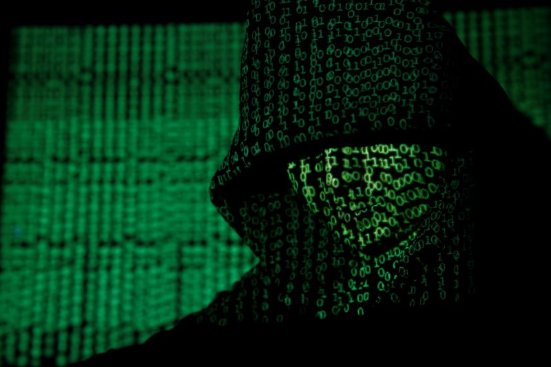 FILE PHOTO: Projection of cyber code on hooded man is pictured in this illustration picture
