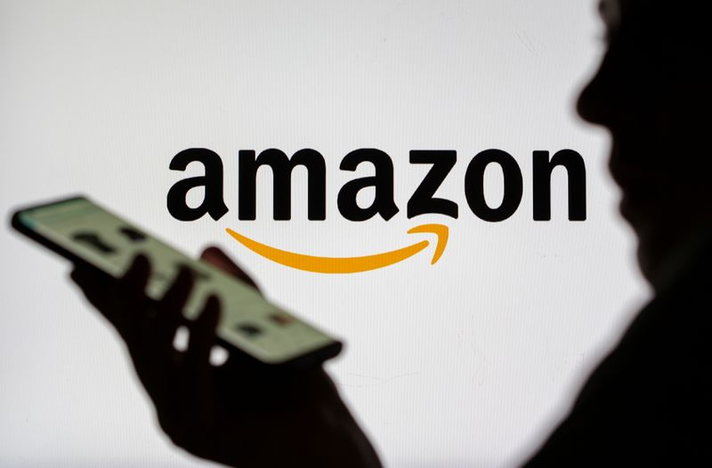 FILE PHOTO: Woman with smartphone is seen in front of displayed Amazon logo in this illustration taken