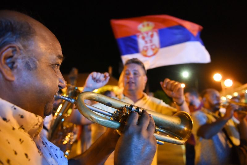 People sing and dance on a street during the annual brass band festival, in Guca
