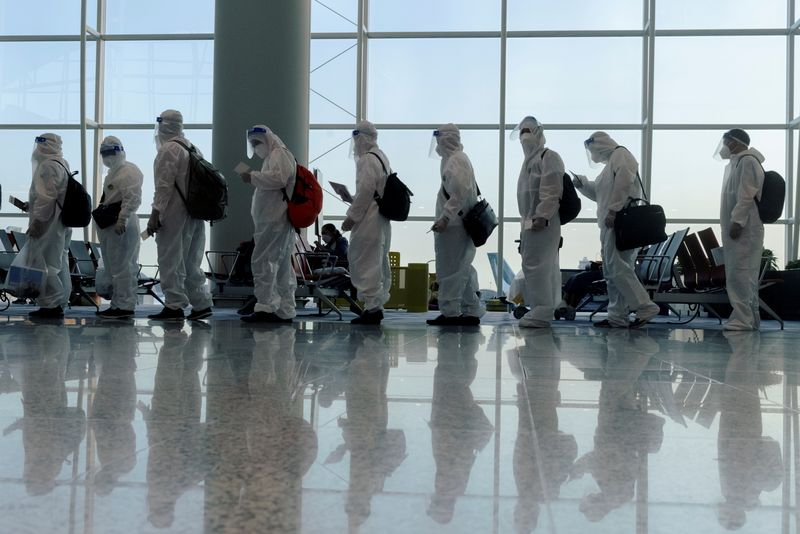 FILE PHOTO: Passengers wearing protective suits (PPE) line up to board their plane for an international flight at Hong Kong airport