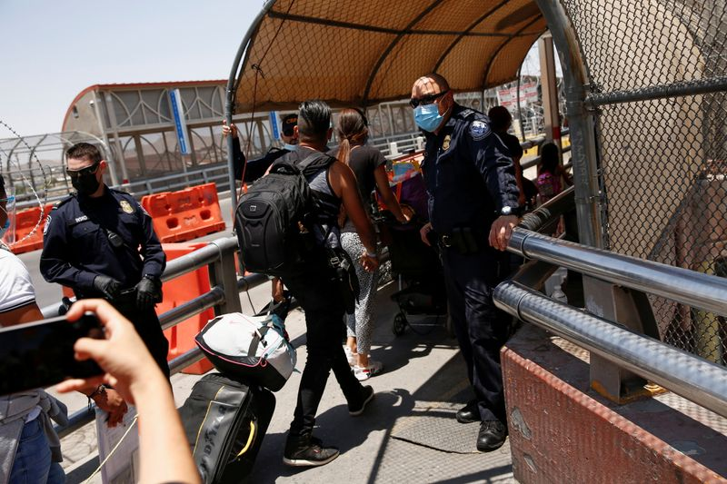 FILE PHOTO: Asylum seekers, under the Migrant Protection Protocols (MPP) program, walk after crossing from Mexico into the U.S. to continue their asylum request in the United States, in this picture taken from Ciudad Juarez