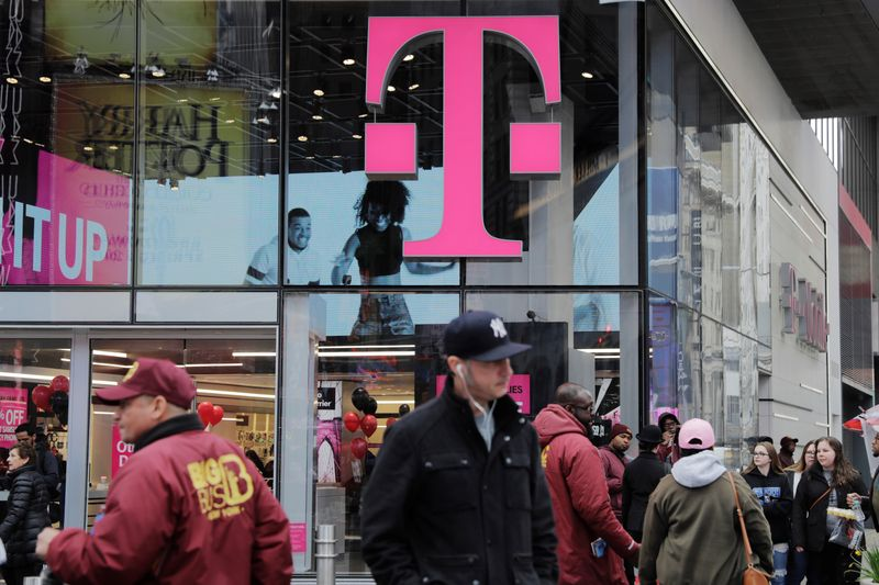 Pedestrians walk past a T-Mobile store in New York