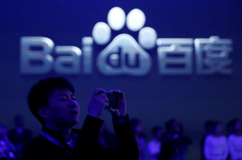 A man takes pictures at the 2018 Baidu World conference and exhibit in Beijing