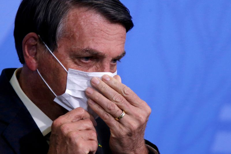 FILE PHOTO: Brazil's  Bolsonaro looks on as he adjusts his protective face mask during a ceremony in Brasilia