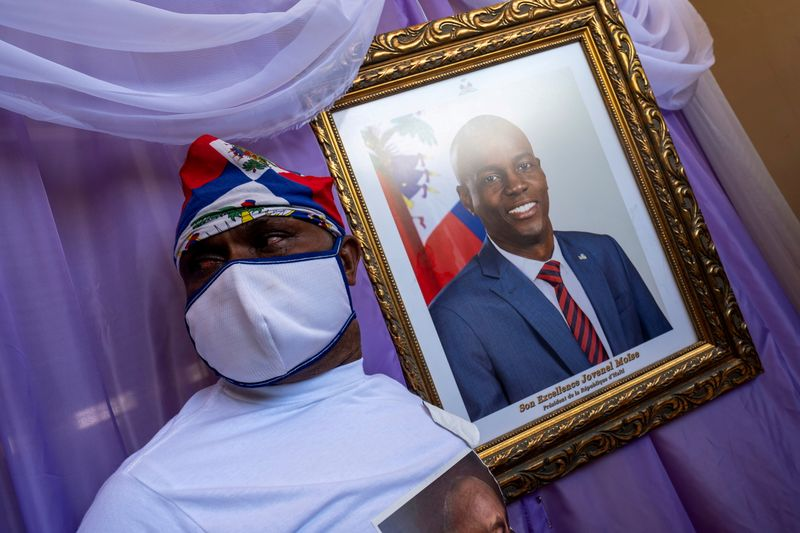 FILE PHOTO: A man stands next to a portrait of slain Haitian President Jovenel Moise placed on a memorial at the city hall in Cap-Haitien