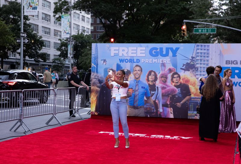 A guest takes a selfie on the red carpet at the premiere for the film