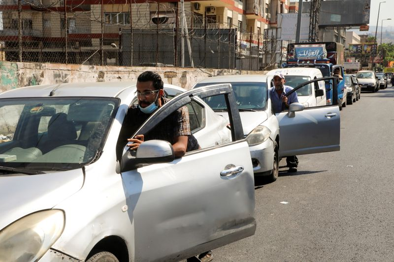 FILE PHOTO: People push their cars due to a lack of fuel, near a gas station in Dora