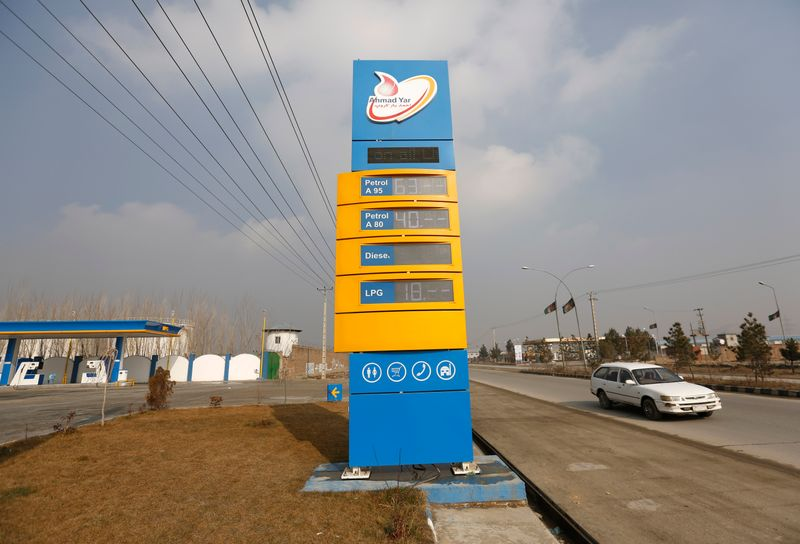 A car pasts behind a oil prices board d at Ahmad Yar Group fuel station shows on outskirt of Kabul