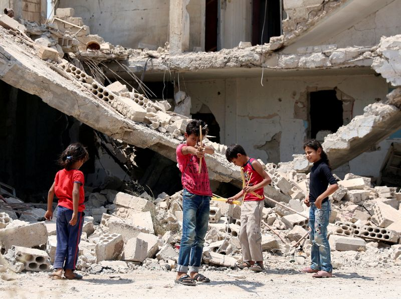 FILE PHOTO: Children play along a street in a rebel-held part of the southern city of Deraa