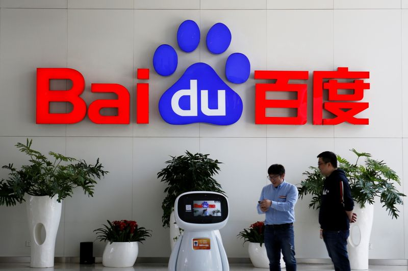FILE PHOTO: Men interact with a Baidu AI robot near the company logo at its headquarters in Beijing
