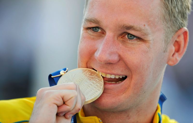 FILE PHOTO: Rickard of Australia bites his gold medal on the podium after setting a new world record in the men's 100m breaststroke swimming final at the World Championships in Rome