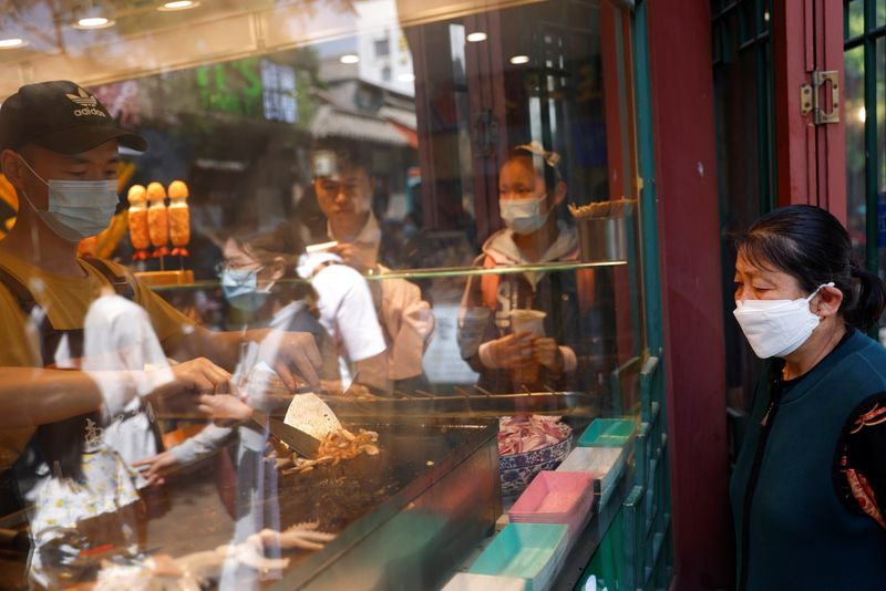 A woman wearing a face mask looks at a man cooking at a restaurant at Nanluoguxiang alley during the Labour Day holiday in Beijing