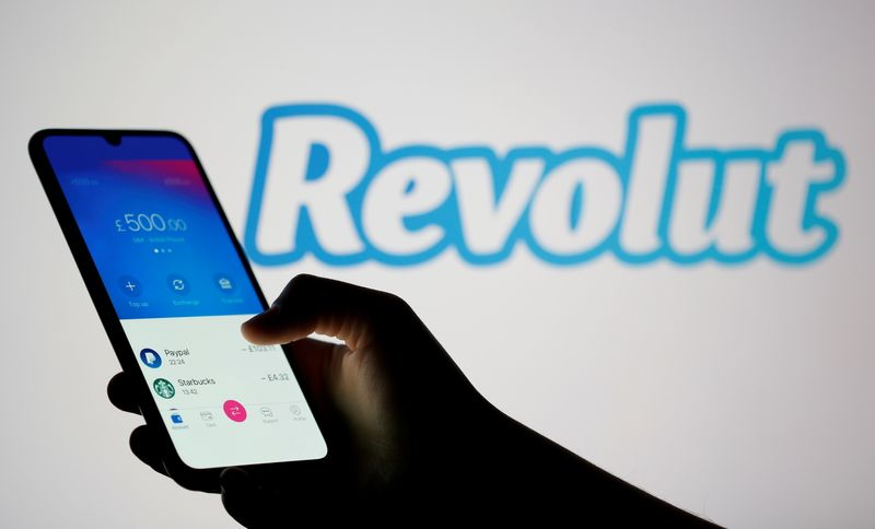 FILE PHOTO: Woman holds smartphone with Revolut app in front of displayed Revolut logo in this illustration