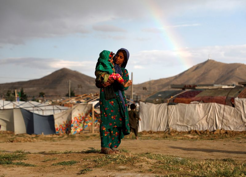 FILE PHOTO: Internally displaced Afghan girl carries a child near their shelter at a refugee camp on the outskirts of Kabul