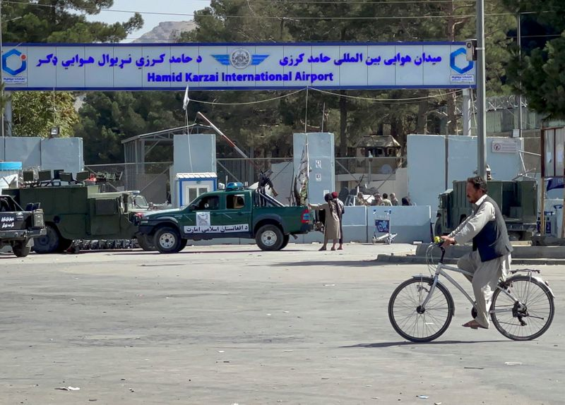 Taliban stand at the entrance gate of Hamid Karzai International airport while Taliban forces block the roads around the airport after yesterday's explosions in Kabul