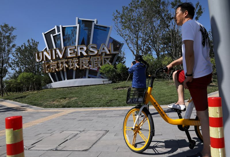 FILE PHOTO: Man rides a bike of a bike-sharing service near a giant sign of Universal Beijing Resort, ahead of its opening, in Beijing