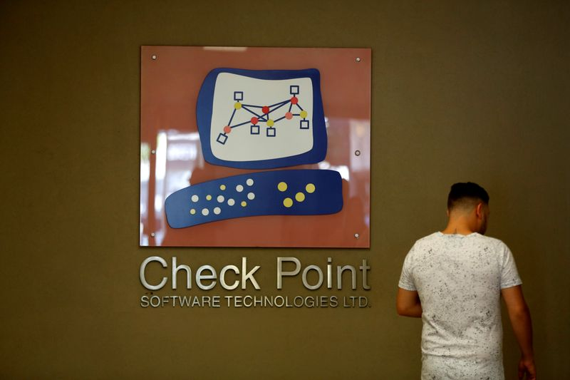 FILE PHOTO: A man stands next to the logo of Check Point Software Technologies at its headquarters in Tel Aviv